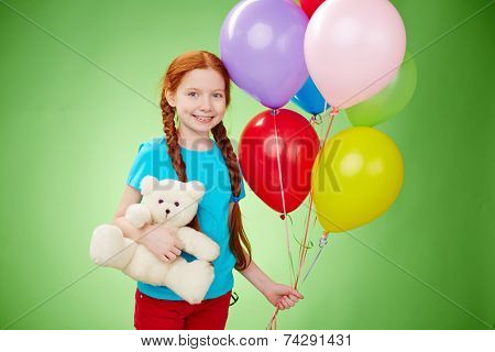Smiling girl with teddybear and balloons looking at camera