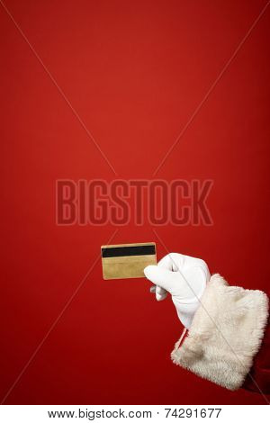 Santa Claus gloved hand holding plastic card over red background