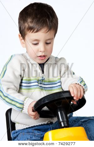 Boy driving a toy car