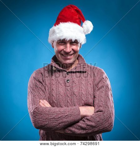 Handsome mid aged man wearing a santa hat while holding his arms crossed. Looking at the camera.
