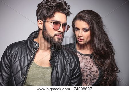 Young fashion couple posing, the man is looking away while the woman is looking at the camera.