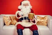 image of christmas claus  - Traditional Santa Claus sitting on the couch watching TV - JPG