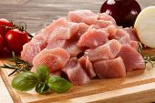 pic of turkey-hen  - Raw turkey meat on cutting board on wooden background - JPG