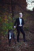 pic of greyhounds  - Young attractive man in suit and tie with a greyhound dog in autumn outdoors - JPG