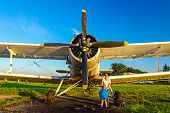 foto of biplane  - Tourists are in front an old biplane standing at sunset - JPG