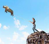 image of rhino  - Young woman holding flying rhino on rope - JPG