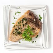 stock photo of swordfish  - Cooked peppered swordfish steak with a parsley and garlic butter sauce on a plate viewed from above - JPG