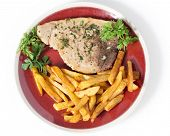 stock photo of swordfish  - Swordfish steak cooked on a plate with french fries and a parsley and garlic butter sauce seen from above - JPG