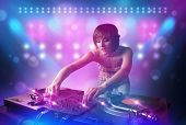 pic of disc jockey  - Pretty young disc jockey mixing music on turntables on stage with lights and stroboscopes - JPG