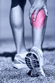 Постер, плакат: Muscle injury Man running clutching calf muscle after spraining it while out jogging on the beach