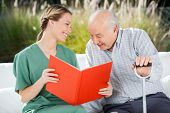 picture of nursing  - Smiling female nurse looking at senior man while reading book in nursing home - JPG