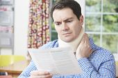 stock photo of human neck  - Man Reading Letter After Receiving Neck Injury - JPG