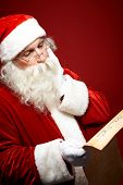 image of letters to santa claus  - Pensive Santa Claus reading Christmas letter - JPG