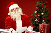 pic of letters to santa claus  - Portrait of confused Santa Claus reading letter - JPG