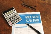 picture of workplace accident  - insurance: blank work injury claim form on desk