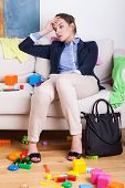 foto of superwoman  - Tired young mother sitting on sofa after hard day at work - JPG