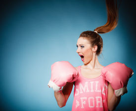 stock photo of hair motion  - Funny girl female boxer in big fun pink gloves playing sports boxing hair motion studio shot blue background - JPG