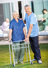 foto of zimmer frame  - Portrait of happy caretaker helping senior woman to use Zimmer frame at nursing home lawn - JPG