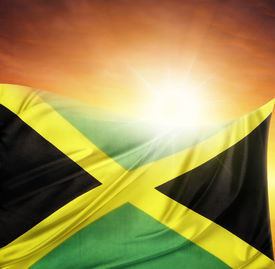 stock photo of jamaican flag  - Jamaican flag in front of bright sky - JPG