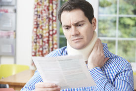 picture of neck brace  - Man Reading Letter After Receiving Neck Injury - JPG