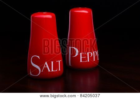 Closeup Of Red Salt-cellar And Pepper-box On Darck Background By Cristina Arpentina