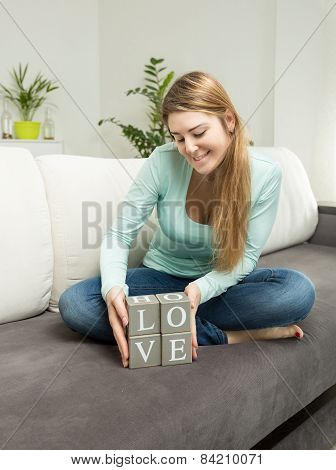 Woman Holding Wooden Bricks With Letters Making Word Love