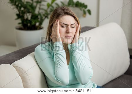 Woman Sitting On Sofa And Suffering From Head Ache