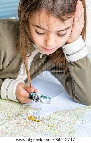 Concentrated Seven Year Old Girl Examining The Map With A Magnifying Glass