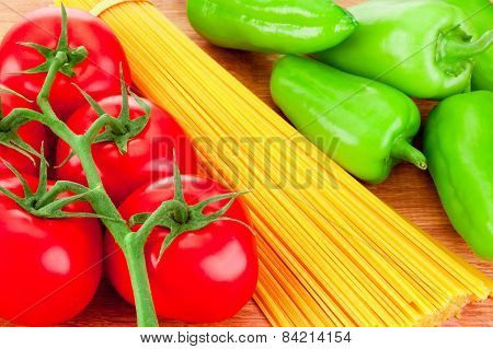 Close-up Spaghetti Pasta, Ripe Tomatoes And Green Peppers On Wooden Board