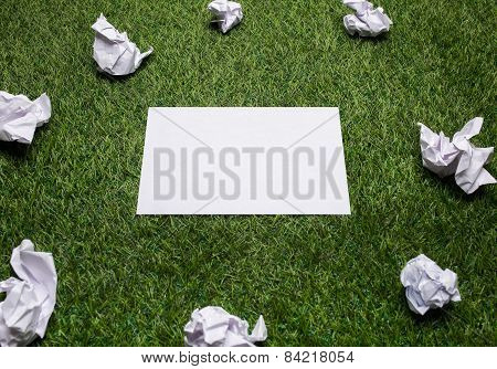White Sheets Of Paper With Crampled Sheets Lying On The Grass