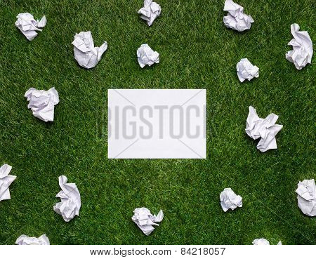 White Sheets Of Paper With Cramled Sheets Lying On The Grass