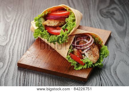 pair of fresh juicy tortilla wraps with chicken and vegetables, on table