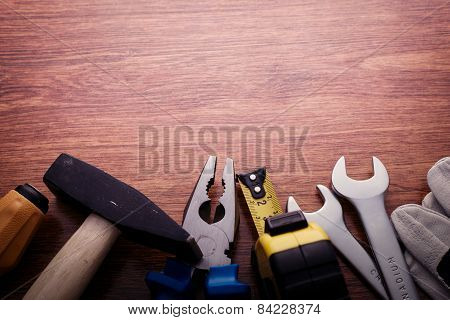 Work Tools At Bottom Border Frame On Wooden Table