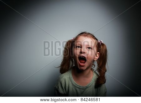 Angry Child Girl Screaming With Opened Mouth And Looking Up With Evil