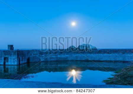 Moon Reflected In A Pool Of Water On Coast