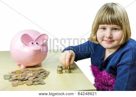 Young girl counting euro coins from piggy bank