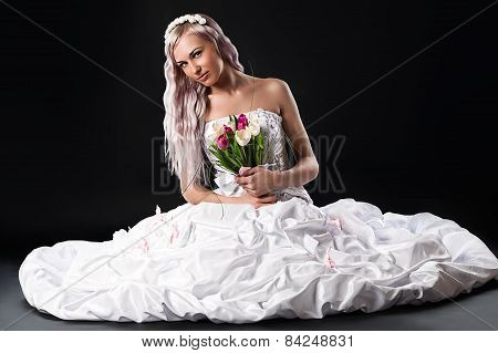 beautiful bride sitting on the floor in a wedding dress