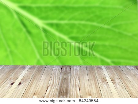 Broad Planks And Green Leaves Of Blur Background.