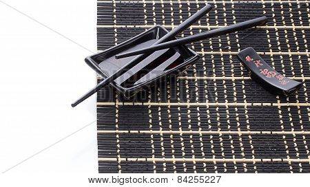 Black Bamboo Mat With Soy Sauce And Chopsticks Over White With Place For Sample Text