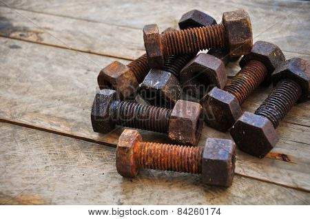 Old bolts or dirty bolts on wooden background, Machine equipment in industry work.