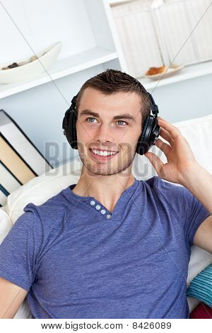 Lively Young Man Listening To Music Sitting On The Couch
