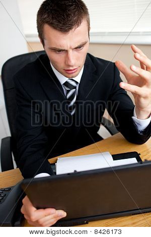 Astonished  Businessman Looking At His Laptop