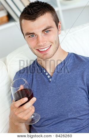 Smiling Young Man Holding A Glass Of Wine Looking At The Camera