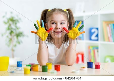cute kid girl  with hands painted in colorful paints