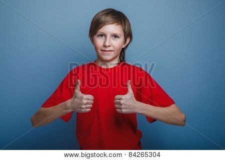 boy teenager European appearance in a green T-shirt showing sign