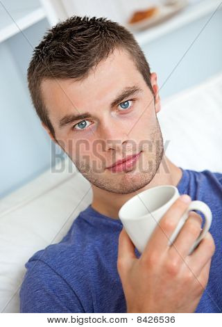 Portrait Of A Serious Young Man Looking At The Camera Holding A Cup