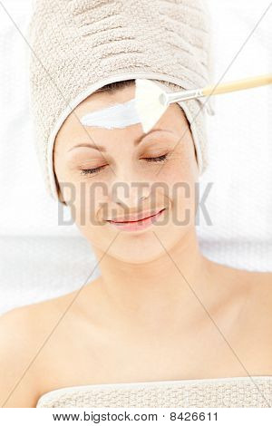 Resting Young Woman Receiving White Cream On Her Face