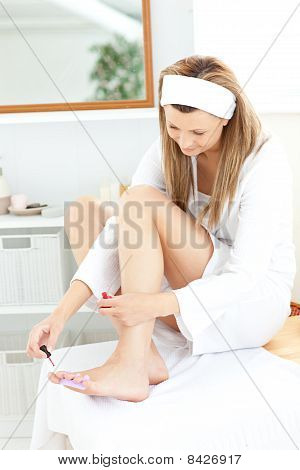 Happy Young Woman Varnishing Her Toenails In The Bathroom