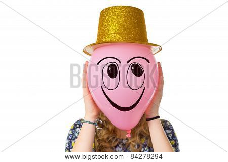 Girl holding balloon with smiling face wearing hat