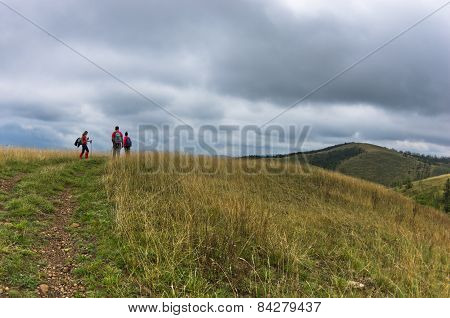 Trekking path through prairie grass at mountains and hills